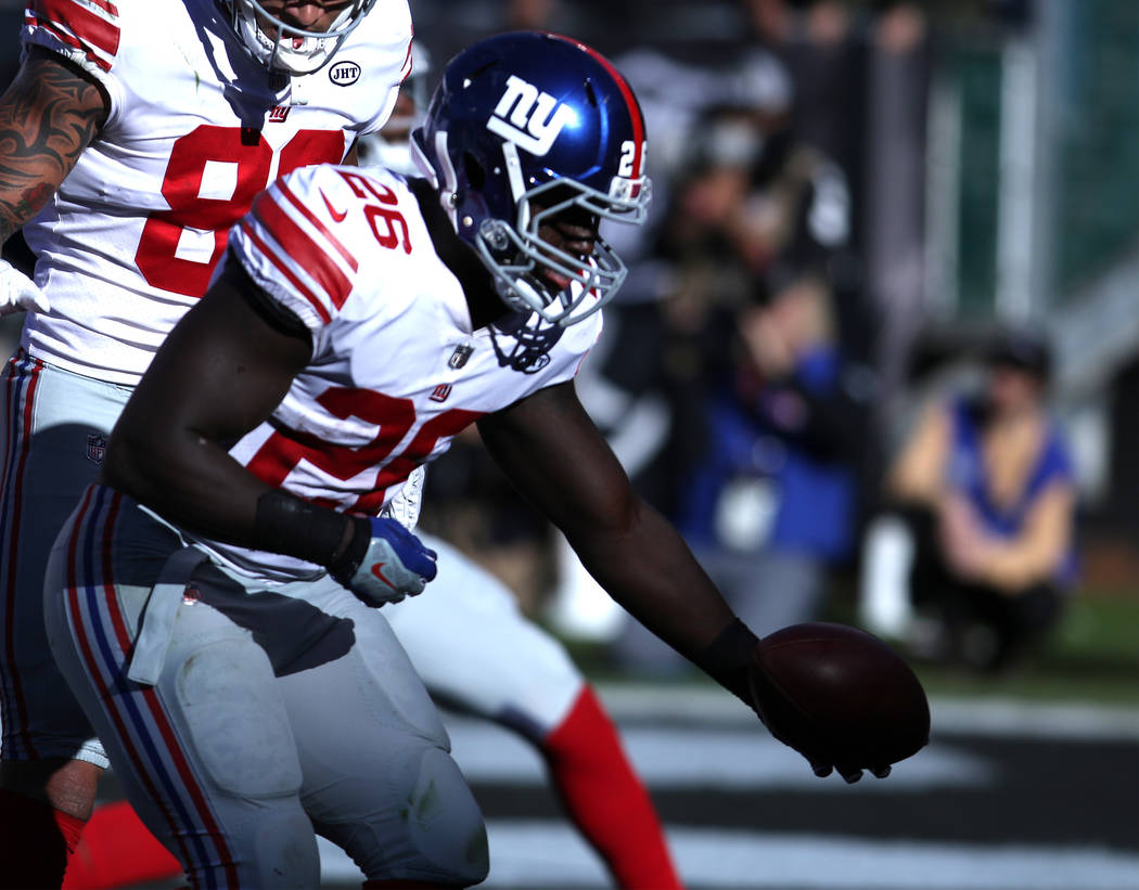 New York Giants running back Orleans Darkwa (26) celebrates a touchdown he scored against the Oakland Raiders during the first half of a NFL game in Oakland, Calif., Sunday, Dec. 3, 2017. Heidi Fa ...