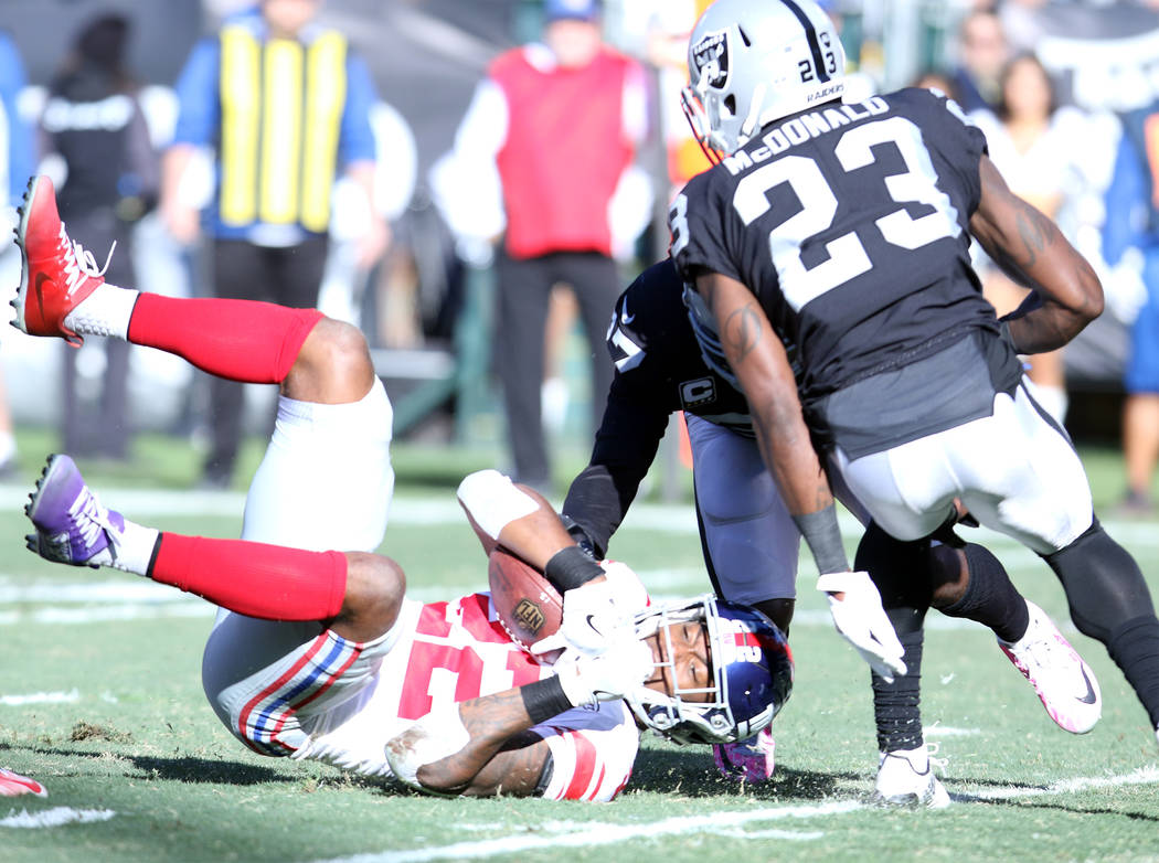 New York Giants running back Wayne Gallman (22) is tackled by Oakland Raiders free safety Reggie Nelson (27) during the first half of a NFL game in Oakland, Calif., Sunday, Dec. 3, 2017. Heidi Fan ...