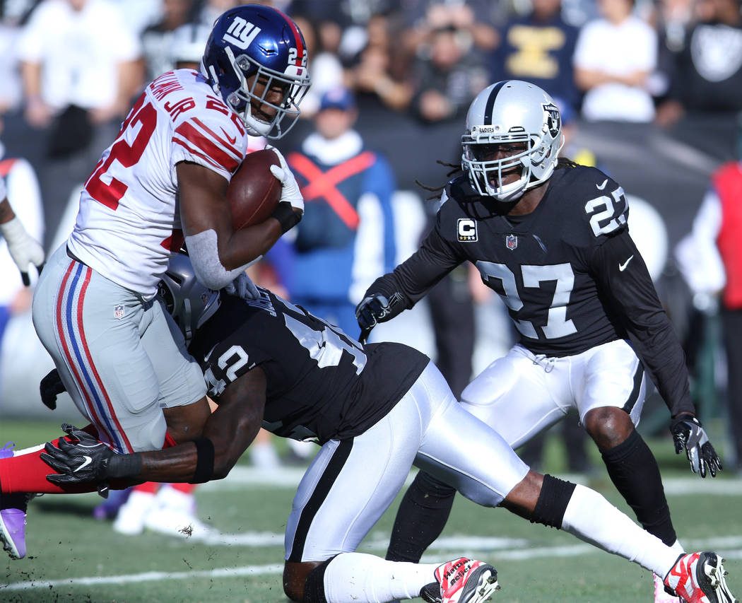 New York Giants running back Wayne Gallman (22) is tackled by Oakland Raiders strong safety Karl Joseph (42) during the first half of a NFL game in Oakland, Calif., Sunday, Dec. 3, 2017. Heidi Fan ...