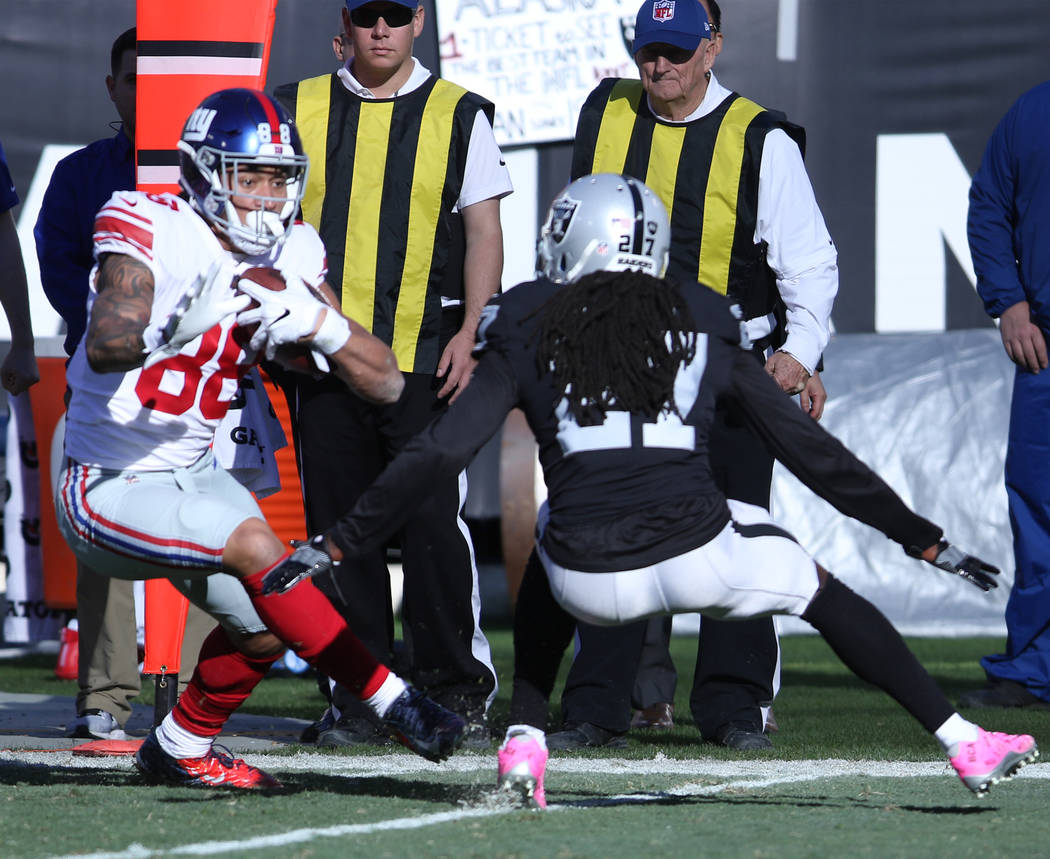New York Giants tight end Evan Engram (88) runs after a catch as Oakland Raiders free safety Reggie Nelson (27) defends during the first half of a NFL game in Oakland, Calif., Sunday, Dec. 3, 2017 ...