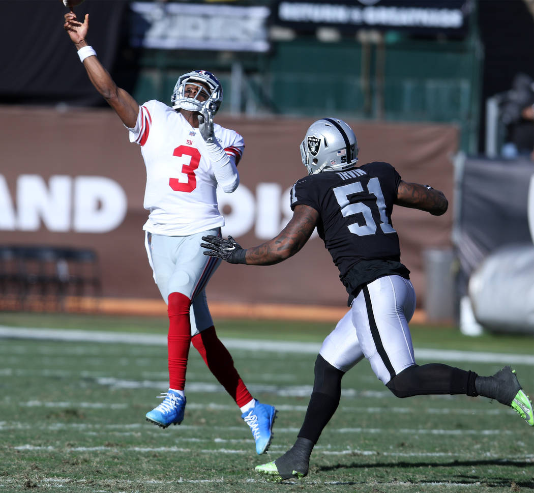 New York Giants quarterback Geno Smith (3) throws the football away as Oakland Raiders outside linebacker Bruce Irvin (51) pressures him during the first half of a NFL game in Oakland, Calif., Sun ...