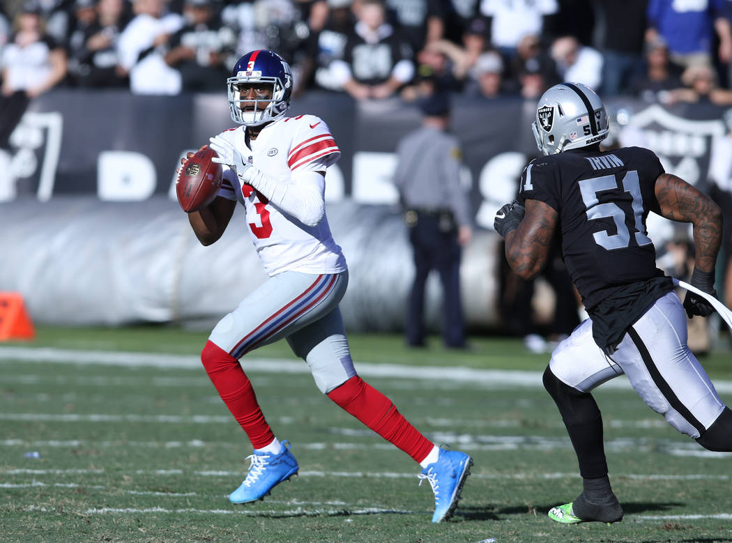 New York Giants quarterback Geno Smith (3) runs with the football as Oakland Raiders outside linebacker Bruce Irvin (51) pressures him during the first half of a NFL game in Oakland, Calif., Sunda ...