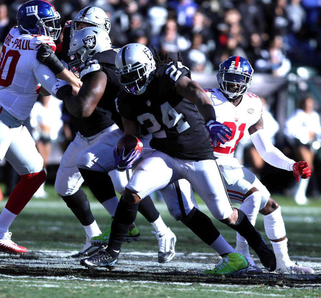 Oakland Raiders running back Marshawn Lynch (24) runs with the football after breaking a tackle from New York Giants strong safety Landon Collins (21) during the first half of a NFL game in Oaklan ...