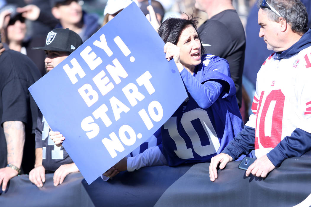 A New York Giants holds up a sign supporting New York Giants quarterback Eli Manning (10), not pictured, before the team's game against the Oakland Raiders in Oakland, Calif., Sunday, Dec. 3, 2017 ...