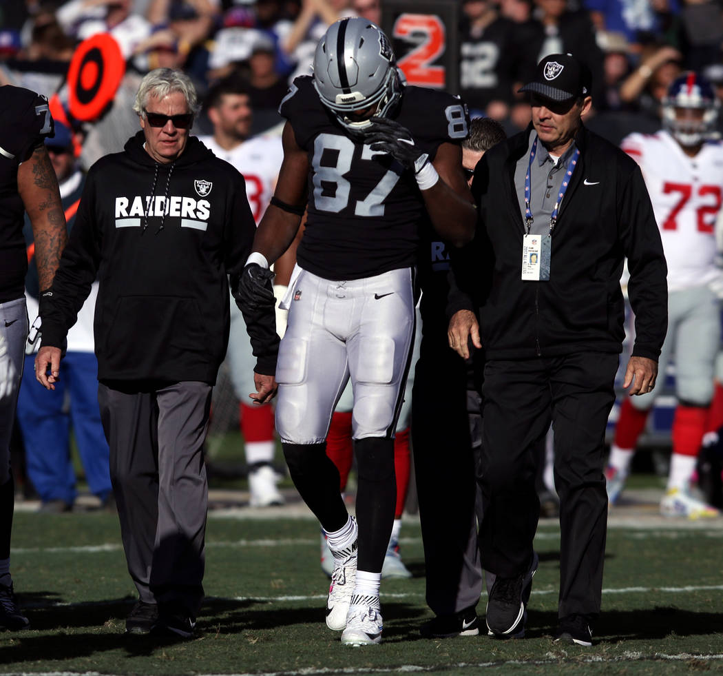 Oakland Raiders tight end Jared Cook (87) walks off the field with trainers after being hurt on a play during the first half of a NFL game against the New York Giants in Oakland, Calif., Sunday, D ...