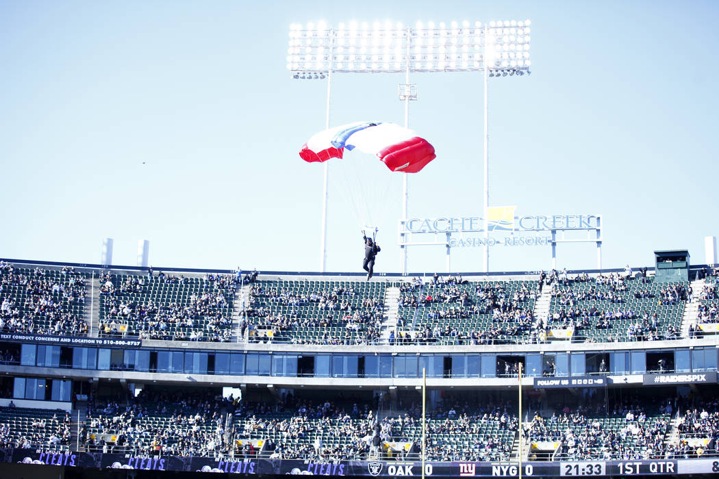 A parachuter prepares to land on the Oakland-Alameda County Coliseum field before the Oakland Raiders NFL game against the New York Giants in Oakland, Calif., Sunday, Dec. 3, 2017. Heidi Fang Las  ...