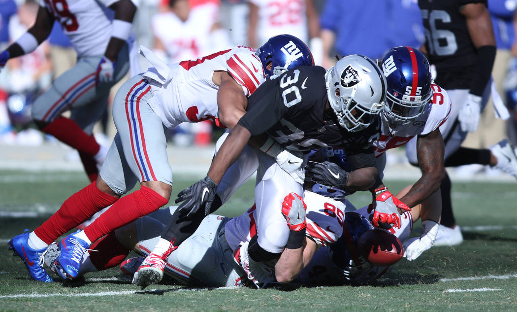 Oakland Raiders running back Jalen Richard (30) fumbles the football on a punt return as New York Giants defenders Ray-Ray Armstrong (55), Rhett Ellison (85) and cornerback Andrew Adams (33) try t ...