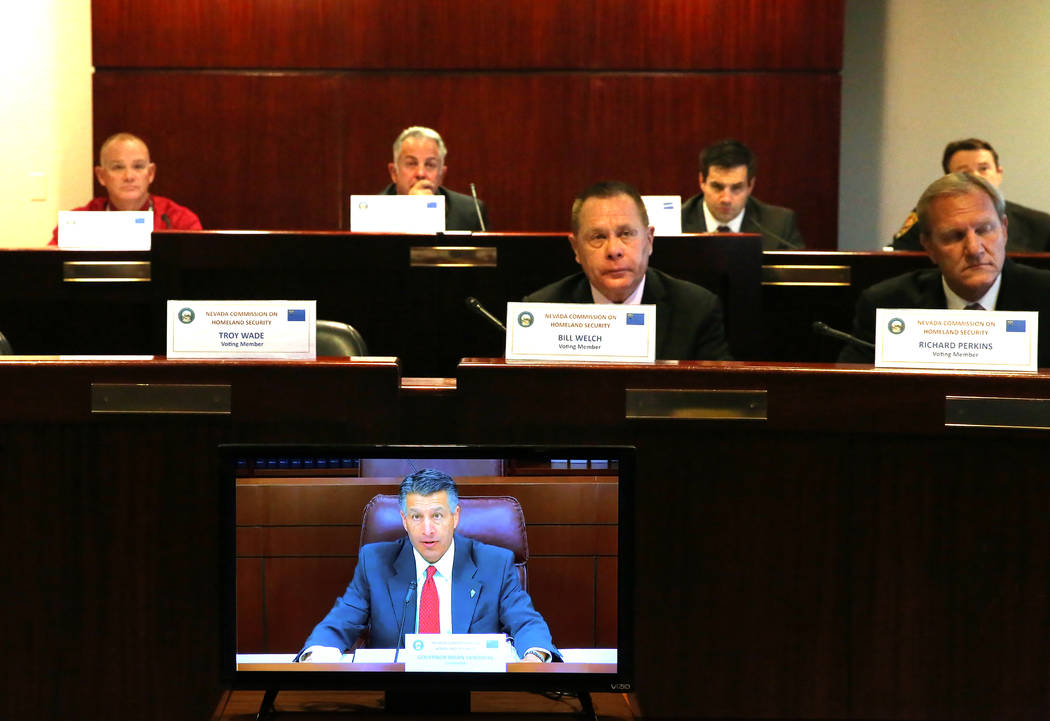 Gov. Brian Sandoval speaks from Carson City, Wednesday, Dec. 6, 2017, during a Nevada Homeland Security Commission meeting regarding the Oct. 1 mass shooting in Las Vegas, as Caleb Cage, chief o ...