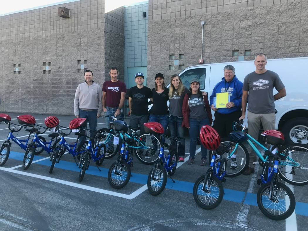 Southern Nevada Biking Coalition members pose for a portrait with Robert Lunt Elementary physical education teacher Chris Regan on Dec. 10, 2017 at 2701 E. Harris Ave. (Kailyn Brown/View)