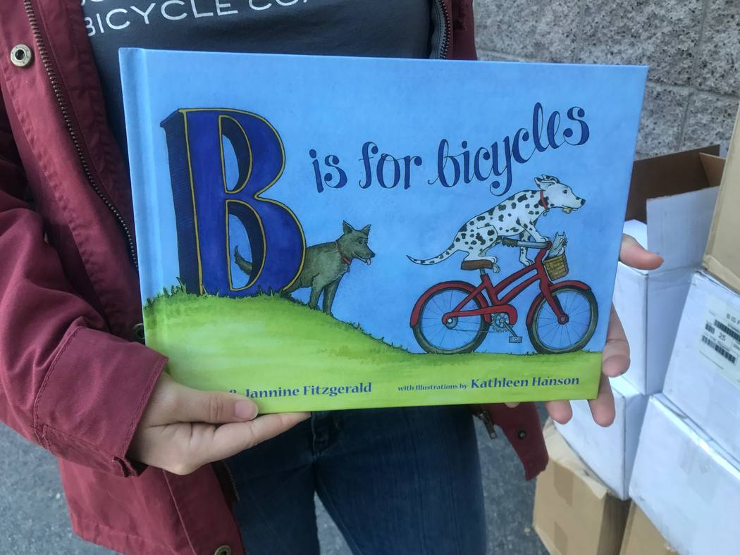 A member of the Southern Nevada Biking Coalition holds a book that the coalition donated to Robert Lunt Elementary School on Dec. 10, 2017 at 2701 E. Harris Ave. (Kailyn Brown/View)