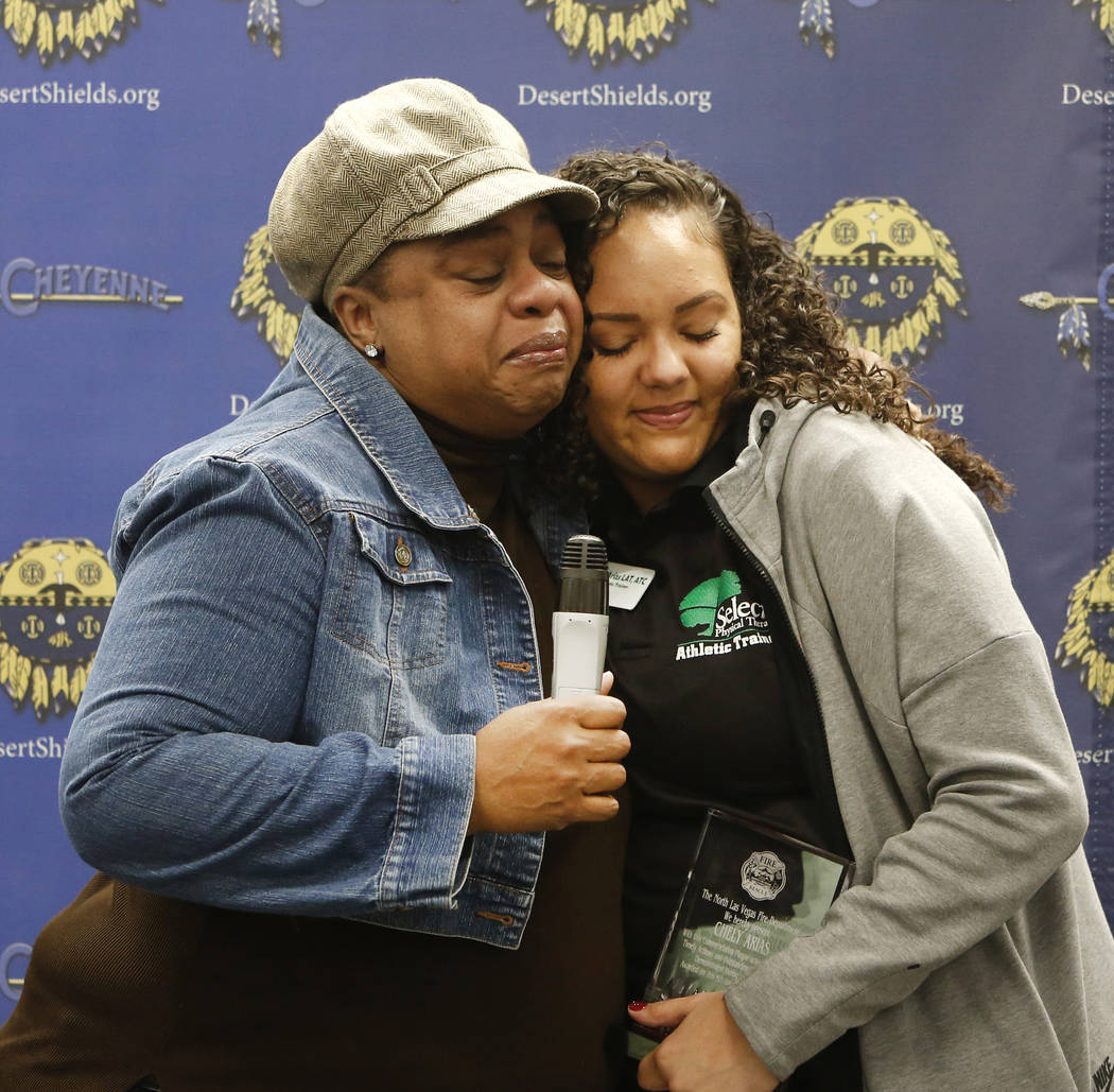 Cheyenne High School Athletic Trainer, Chely Arias, right, hugged by Kimberly Jones, a mother of Kennedi Jones, at the school's library on Wednesday, Dec. 6, 2017, in Las Vegas. Arias was recogniz ...