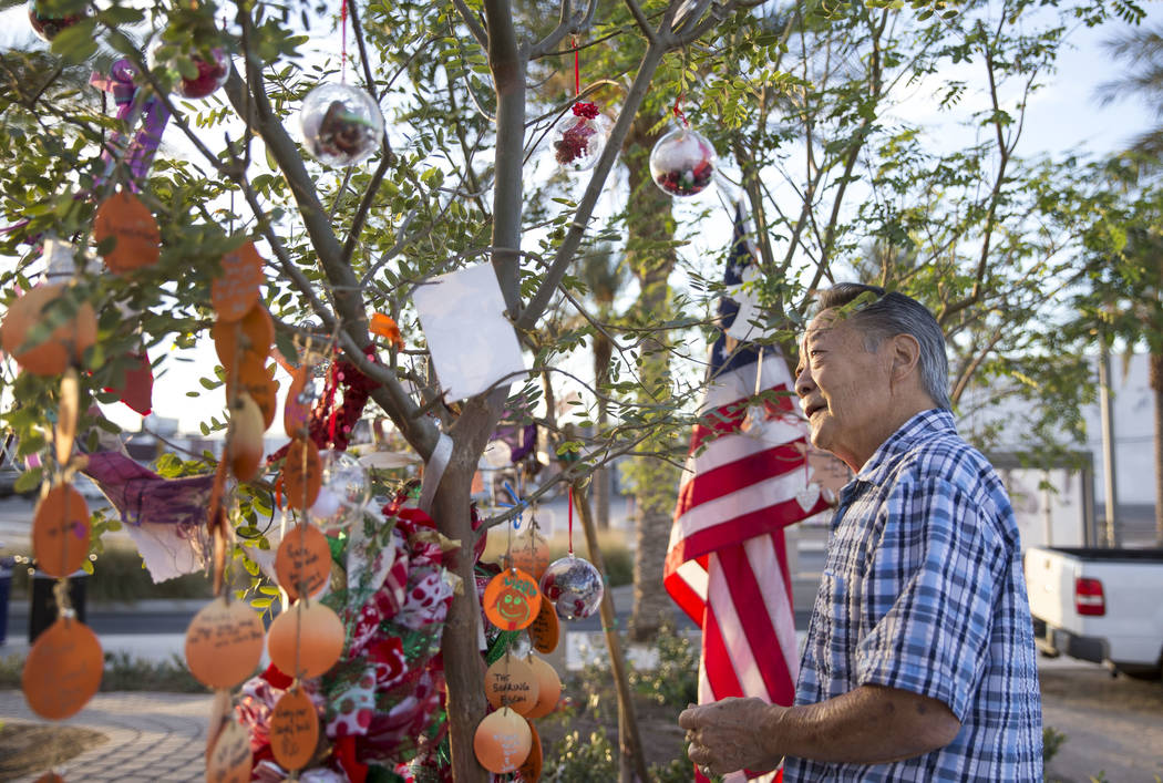 Roger Kimura, uncle of Route 91 Harvest shooting victim Nicol Kimura, hangs ornaments on his niece's tree at the Community Healing Garden in downtown Las Vegas, Thursday, Nov. 30, 2017. Richard Br ...