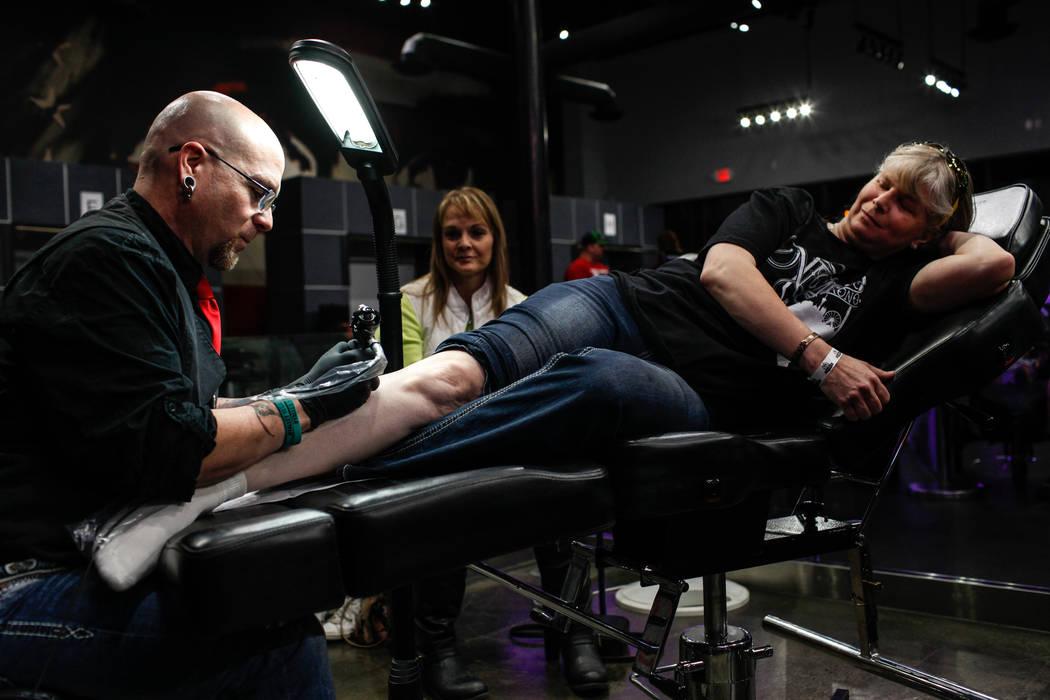 "Walter ""Sausage"" Frank, 47, left, tattoos Jill Flynn, 52, right, both of Las Vegas, at Revolt Tattoos in Las Vegas, Friday, Oct. 27, 2017. Joel Angel Juarez Las Vegas Review-Journal @jajuarezphoto"