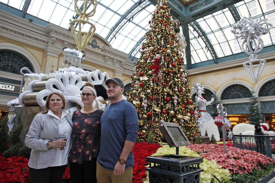 Carol Vallozzi, from left, Hannah Musser, and her husband Rick Musser have their photo taken at the Bellagio Conservatory & Botanical Gardens in Las Vegas, Monday, Dec. 4, 2017. Rachel Aston L ...