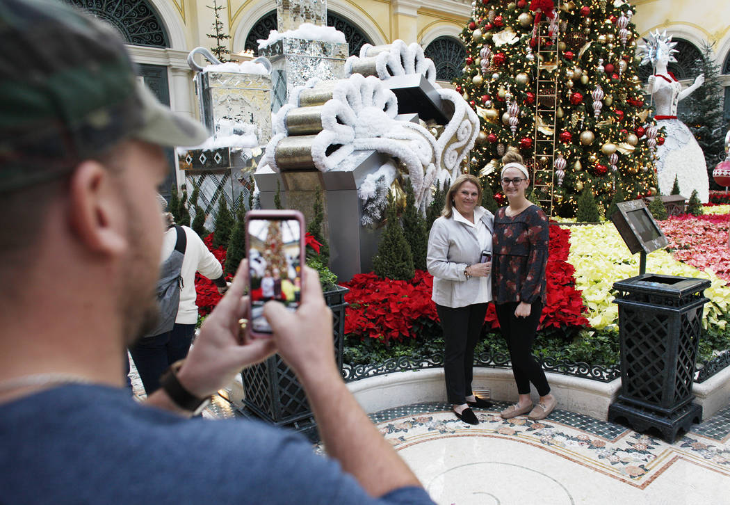 Rick Musser takes a photo of Carol Vallozzi, left, and his wife Hannah Musser at the Bellagio Conservatory & Botanical Gardens in Las Vegas, Monday, Dec. 4, 2017. Rachel Aston Las Vegas Review ...