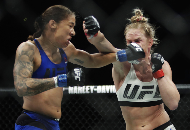 Germaine de Randamie, left, of the Netherlands, punches Holly Holm during a women's featherweight championship mixed martial arts bout at UFC 208 early Sunday, Feb. 12, 2017, in New York. De Randa ...
