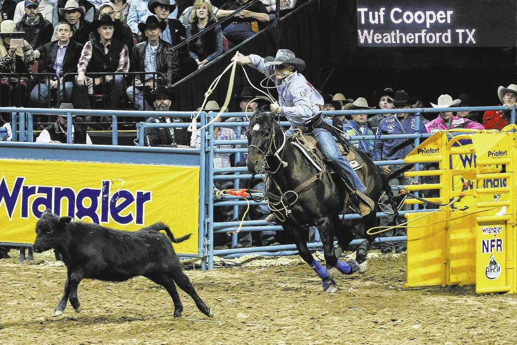 Tuf Cooper of Weatherford, Texas chases a steer in the tie-down roping event during the third night of the 59th Wrangler National Finals Rodeo at the Thomas & Mack Center in Las Vegas, Saturda ...