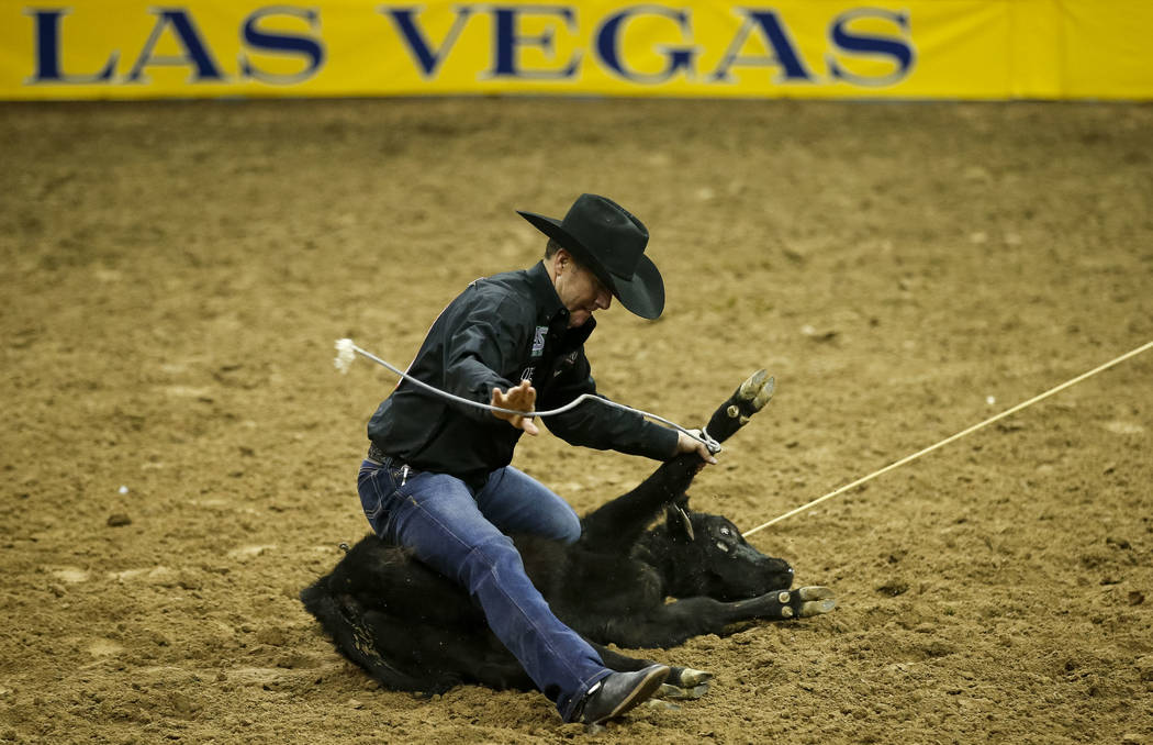Trevor Brazile of Decatur, Texas takes part in the tie-down roping competition during the ninth go-round of the National Finals Rodeo, Friday, Dec. 15, 2017, at the Thomas & Mack Center in Las ...
