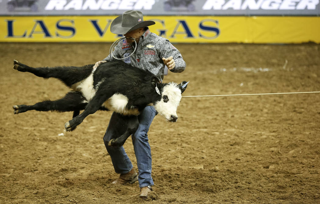 Tuf Cooper of Weatherford, Texas takes part in the tie-down roping competition during the ninth go-round of the National Finals Rodeo, Friday, Dec. 15, 2017, at the Thomas & Mack Center in Las ...