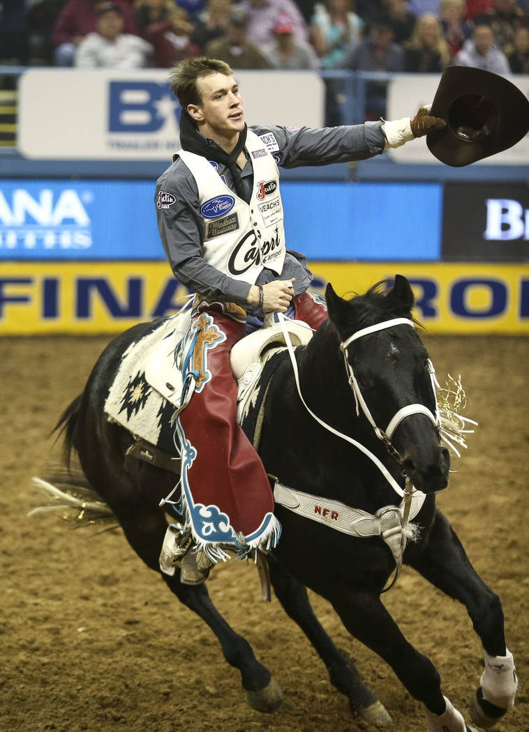 Tim O'Connell of Zwingle, Iowa takes a victory lap on Mucho Dinero after riding in the bareback competition in the tenth go-round of the National Finals Rodeo, Saturday, Dec. 16, 2017, at the Thom ...