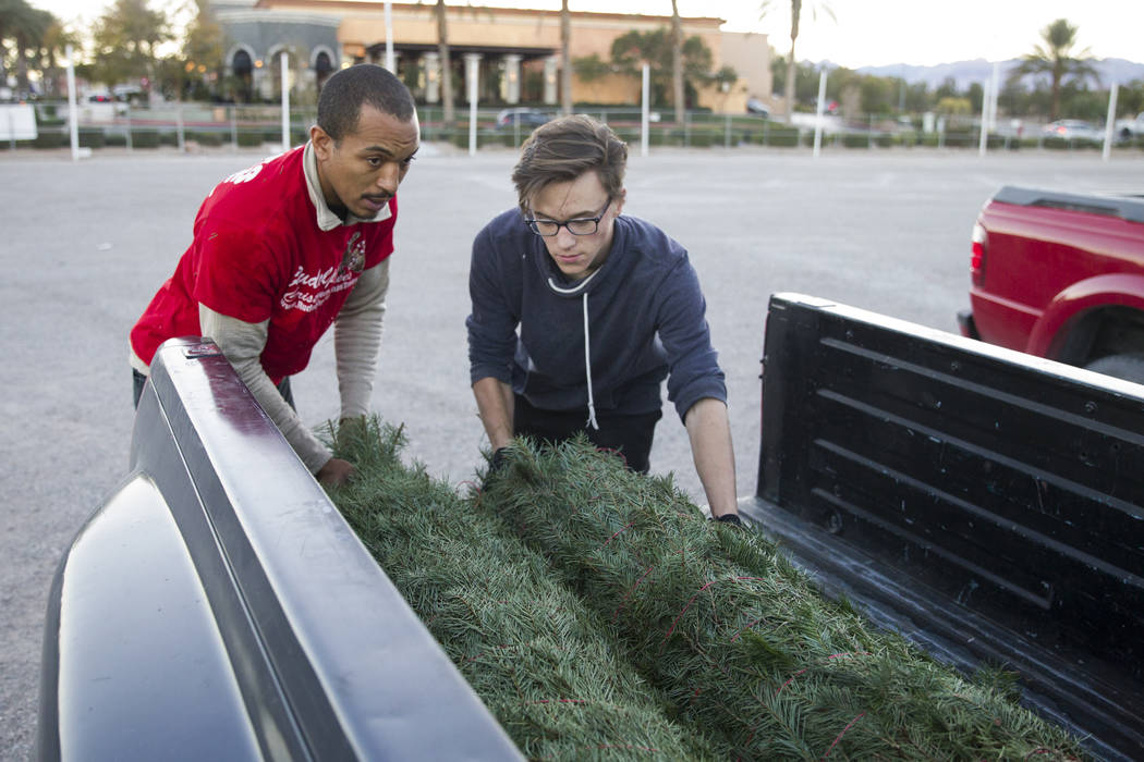 Ed Brown, left, and Nikolai Baron, load two Christmas trees on the truck of a customer at Rudolph's Christmas Trees near the intersection of Alta Drive and Rampart Boulevard in Las Vegas, Wednesda ...