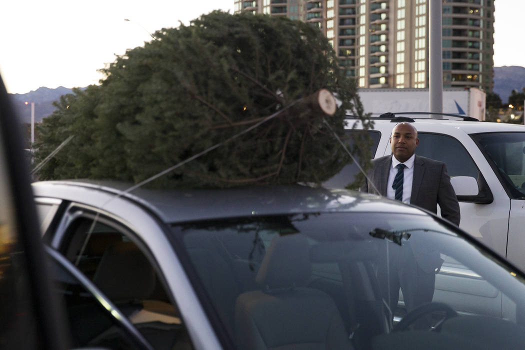 Ben McFarlane waits as his Christmas tree is loaded on the roof of his car at Rudolph's Christmas Trees near the intersection of Alta Drive and Rampart Boulevard in Las Vegas, Wednesday, Dec. 6, 2 ...