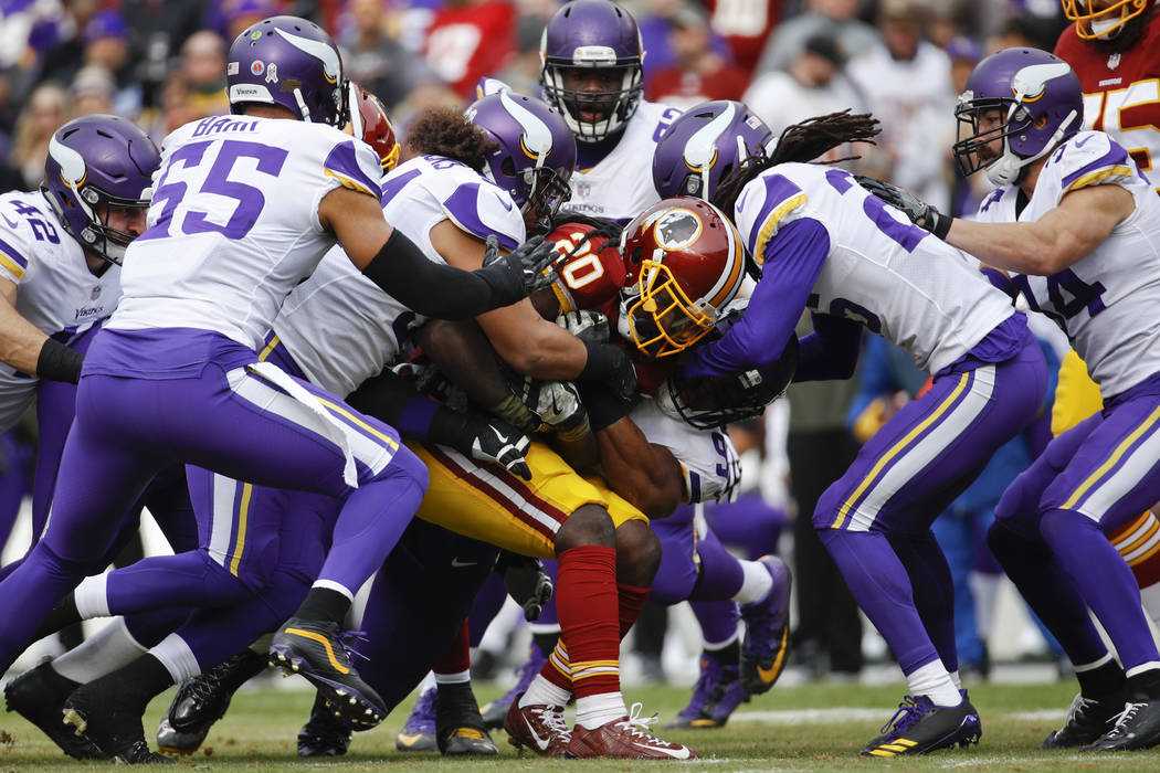 Washington Redskins running back Rob Kelley (20) is swarmed by the Minnesota Vikings defense during the first half of an NFL football game in Landover, Md., Sunday, Nov. 12, 2017. (AP Photo/Patric ...