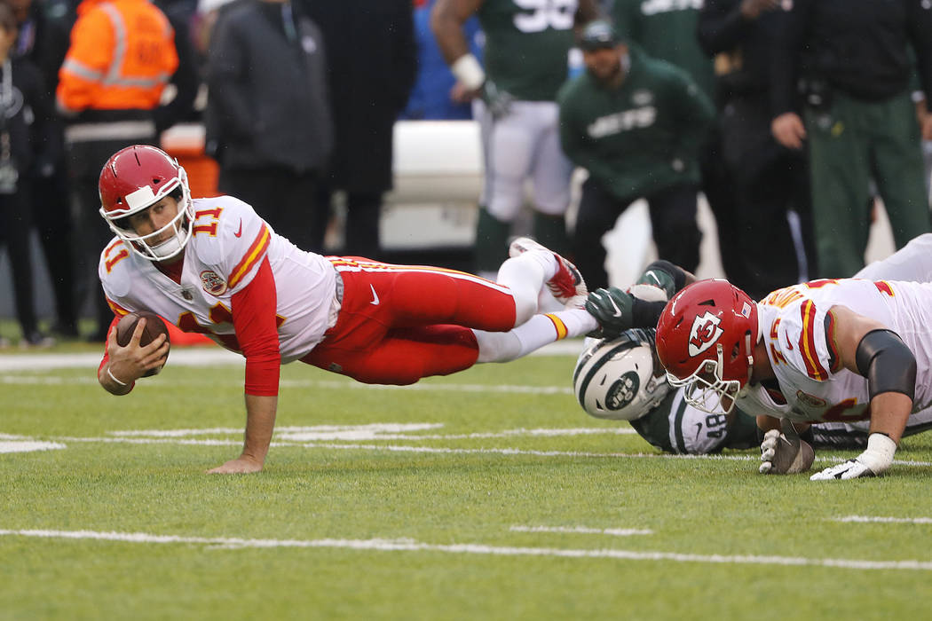 Kansas City Chiefs quarterback Alex Smith, left, dives for extra yards during the first half of an NFL football game against the New York Jets, Sunday, Dec. 3, 2017, in East Rutherford, N.J. (AP P ...