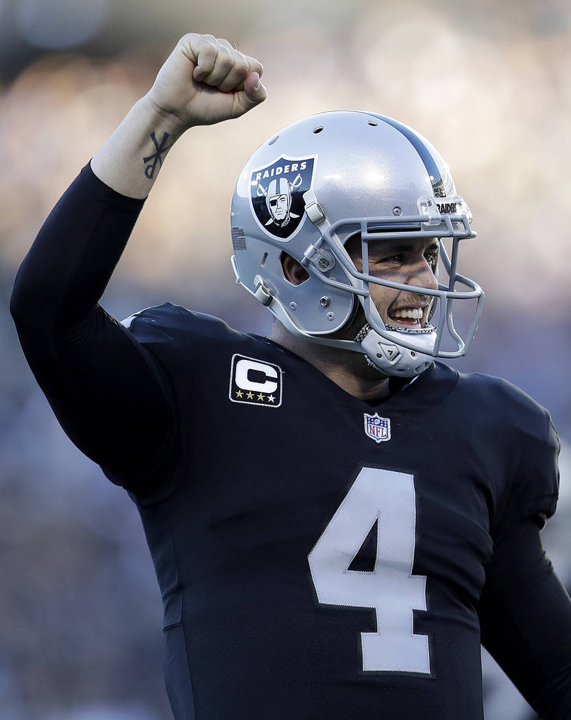 Oakland Raiders quarterback Derek Carr (4) celebrates after running back DeAndre Washington scored a touchdown during the second half of an NFL football game against the New York Giants in Oakland ...