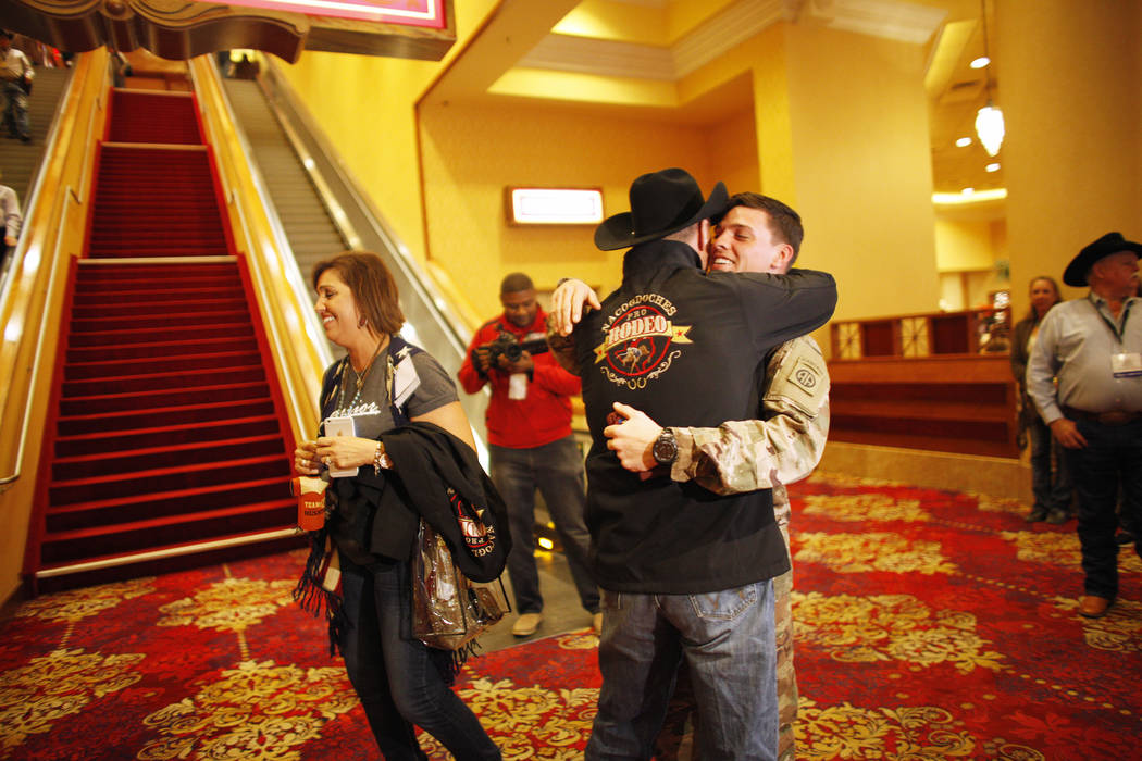 Bo Scott, left,  hugs his stepson Sgt. Timothy Grace as his mom, Anita Scott, stands nearby at the South Point in Las Vegas, Tuesday, Dec. 5, 2017. Anita arranged to surprise Bo of Grace's return  ...