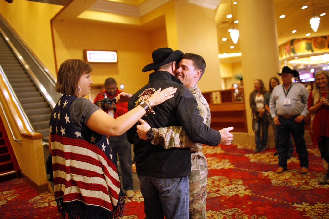 Bo Scott, left,  hugs his stepson Sgt. Timothy Grace as his mom, Anita Scott, pats Bo's back at the South Point in Las Vegas, Tuesday, Dec. 5, 2017. Anita arranged to surprise Bo of Grace's return ...