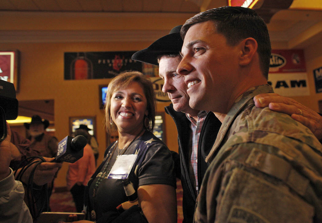 Anita Scott, from left, her husband Bo Scott, and Sgt. Timothy Grace talk to the media at the South Point in Las Vegas, Tuesday, Dec. 5, 2017. Anita, Grace's mom, arranged to surprise Bo, Grace's  ...