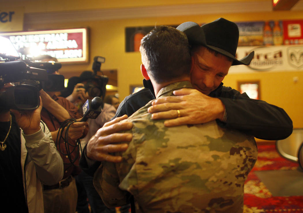 Bo Scott, left,  hugs his stepson Sgt. Timothy Grace as his mom, Anita Scott, hugs him too at the South Point in Las Vegas, Tuesday, Dec. 5, 2017. Anita arranged to surprise Bo of Grace's return f ...