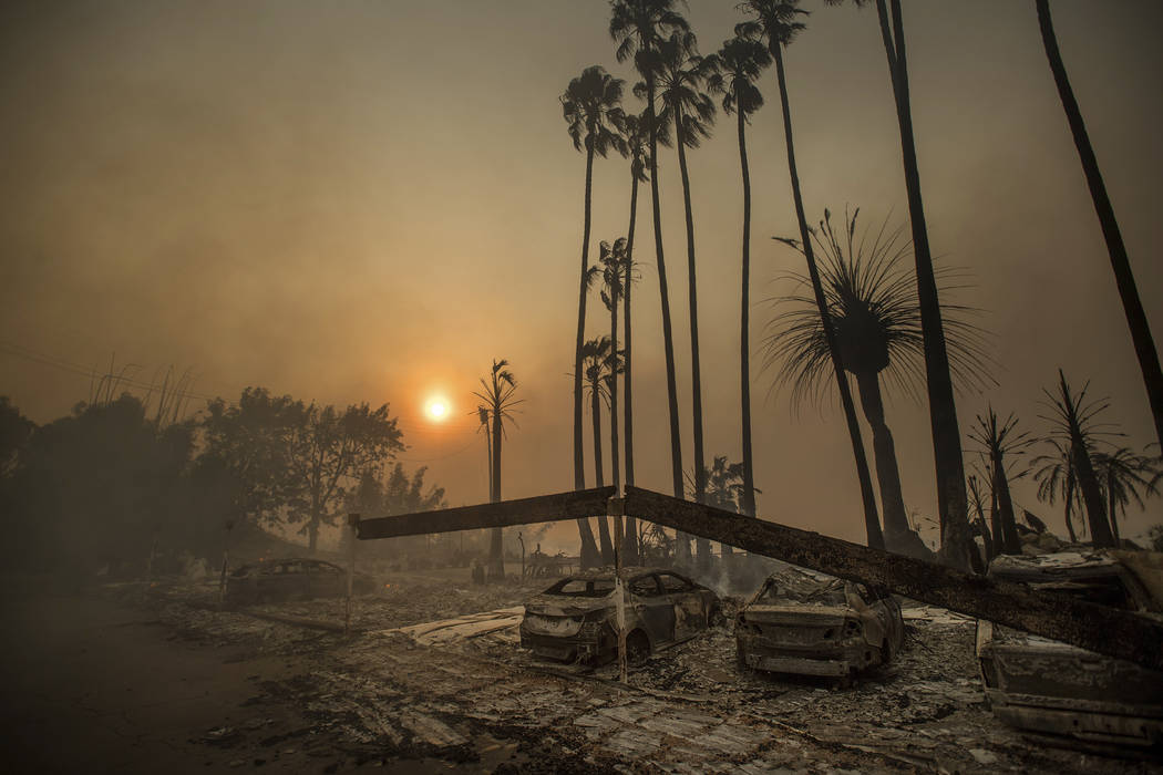 Smoke rises behind a leveled apartment complex as a wildfire burns in Ventura, Calif., on Tuesday, Dec. 5, 2017. Over 100 structures have burned so far in Ventura County, officials said.  (Noah Be ...