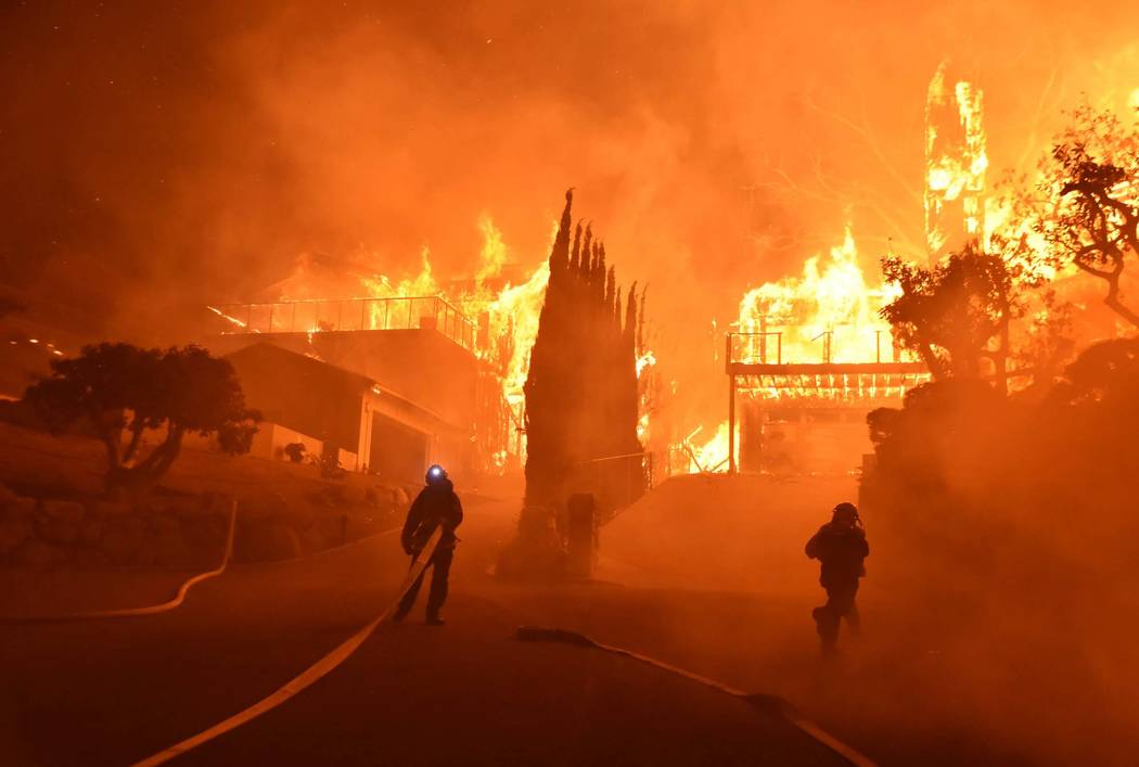 In this photo provided by the Ventura County Fire Department, firefighters work to put out a blaze burning homes early Tuesday, Dec. 5, 2017, in Ventura, Calif. Authorities said the blaze broke ou ...