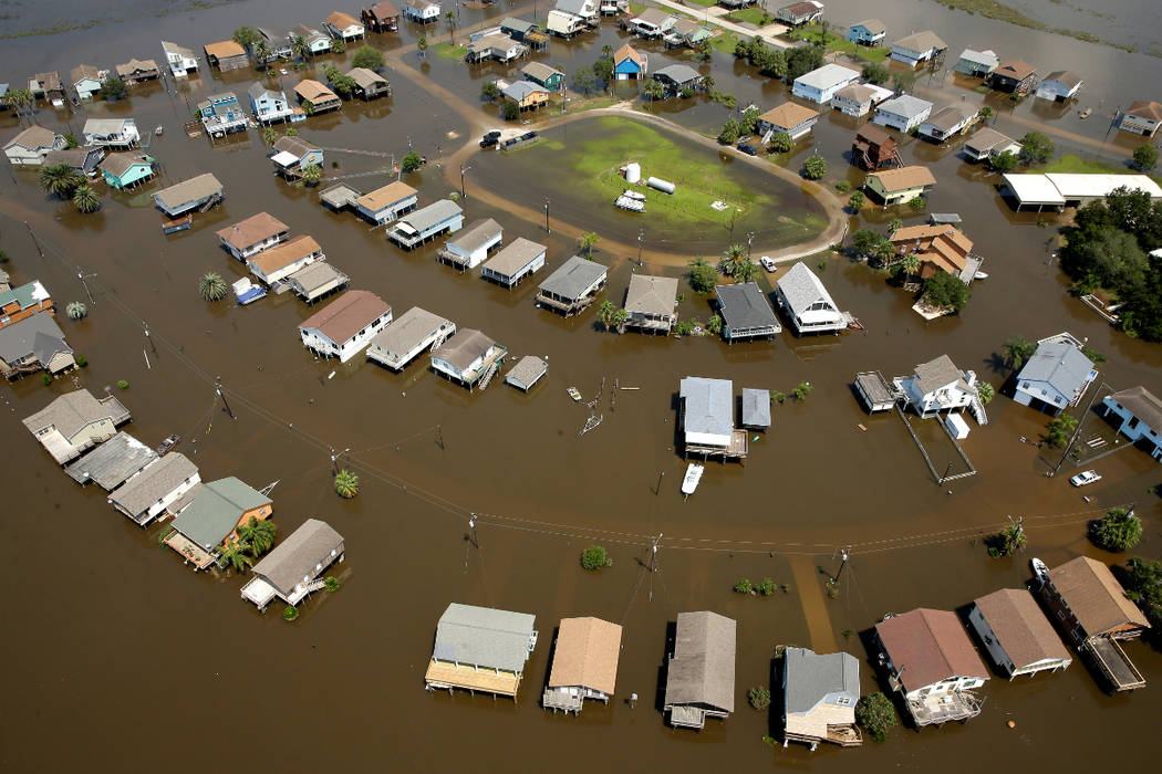 Homes are surrounded by floodwater Sept. 1, 2017, in the aftermath of Hurricane Harvey near Galveston, Texas. More than three months after Hurricane Harvey walloped Texas, many affected residents  ...