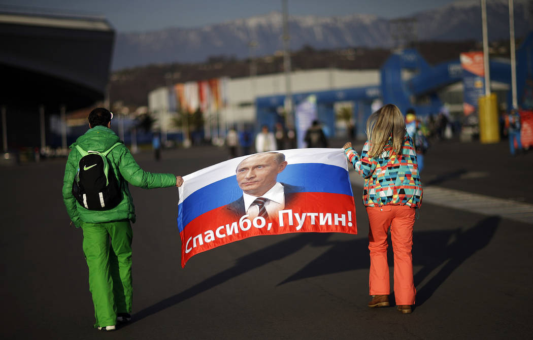 "Veleriya Obarevich, right, and Yan Shamilov carry a Russian flag with the message ""Thank you, Putin!"" written across it in Russian through Olympic Park ahead of the 2014 Winter Olympics closing ce ..."