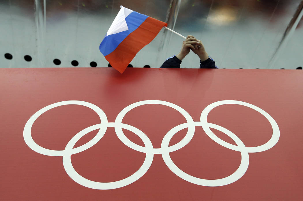 A Russian skating fan holds the country's national flag over the Olympic rings before the start of the men's 10,000-meter speedskating race at Adler Arena Skating Center during the 2014 Winter Oly ...