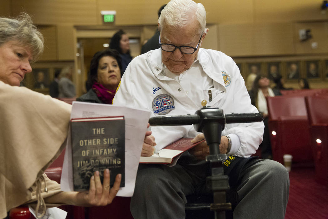 Pearl Harbor survivor Lt. Jim Downing signs copies of his book before getting recognized during a Las Vegas City Council meeting at Las Vegas City Hall, Wednesday, Dec. 6, 2017. (Erik Verduzco/Las ...
