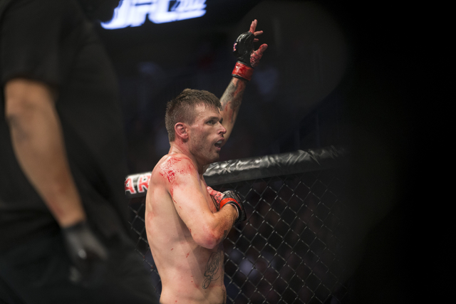 Tim Means raises his arm in victory after winning by a second round technical knockout against Sabah Homasi in the welterweight bout during UFC 202 at T-Mobile Arena on Saturday, Aug. 20, 2016, in ...