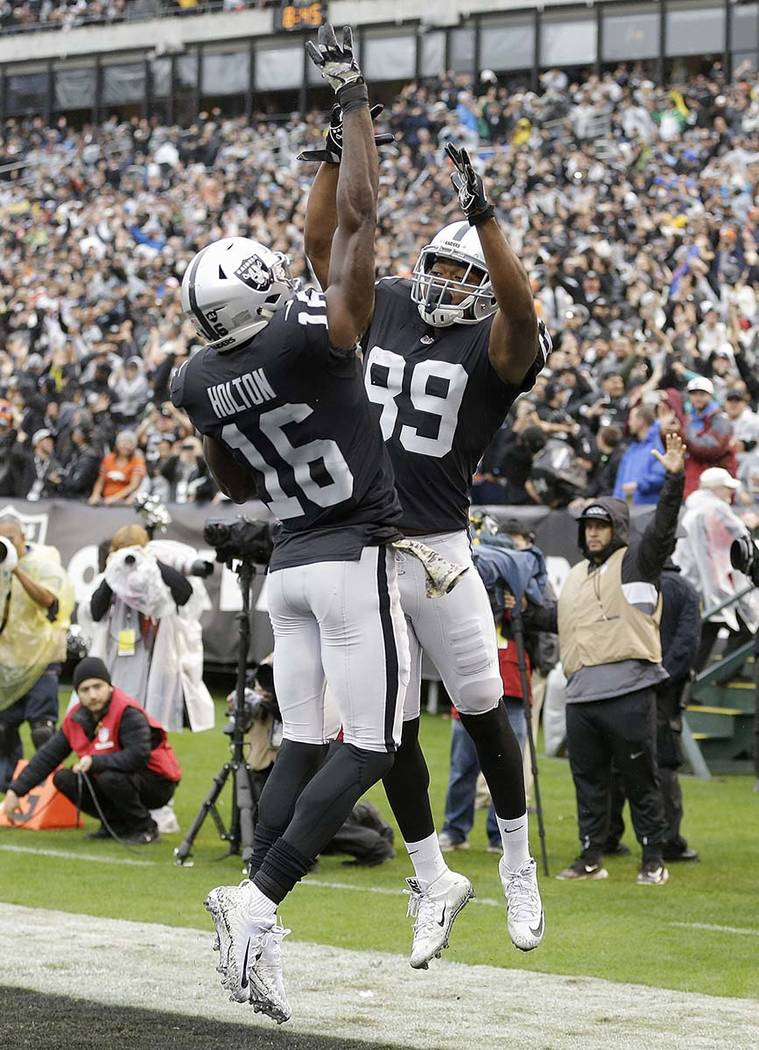 Oakland Raiders wide receiver Amari Cooper (89) celebrates after scoring a touchdown with wide receiver Johnny Holton (16) during the first half of an NFL football game against the Denver Broncos  ...