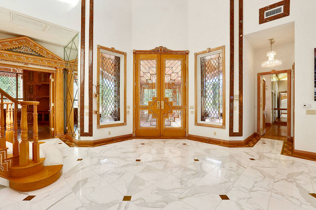The entry greets guests with polished, white marble floors and white walls that provide a striking contrast to the custom wood work and gold accents. (Luxury Estates International)