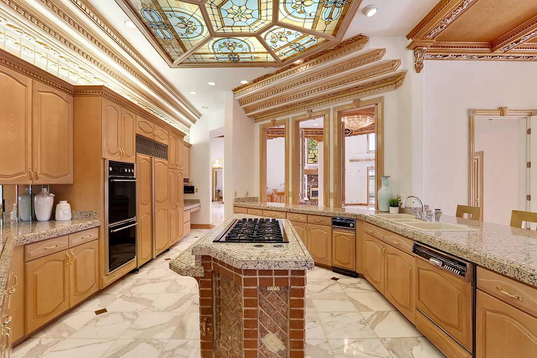 The gourmet kitchen is clad with premium finishes, modern appliances and a triple-coffered ceiling with wood and brass accents. (Luxury Estates International)