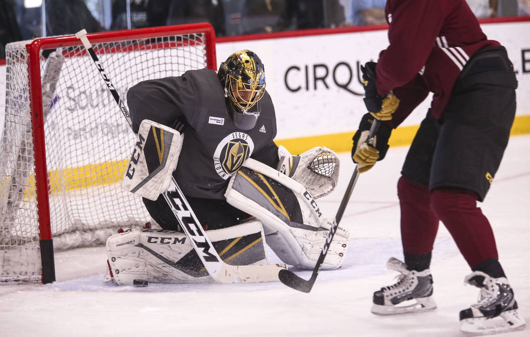 Vegas Golden Knights goalie Marc-Andre Fleury, left, deflects the puck in a drill during the NHL team's practice at the City National Arena in Las Vegas, Wednesday, Dec. 6, 2017. Richard Brian Las ...