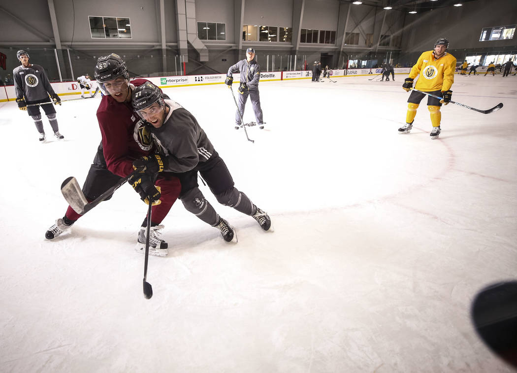 Vegas Golden Knights left wing David Perron (57) and defenseman Brad Hunt (77) vie for the puck during the NHL team's practice at the City National Arena in Las Vegas, Wednesday, Dec. 6, 2017. Ric ...