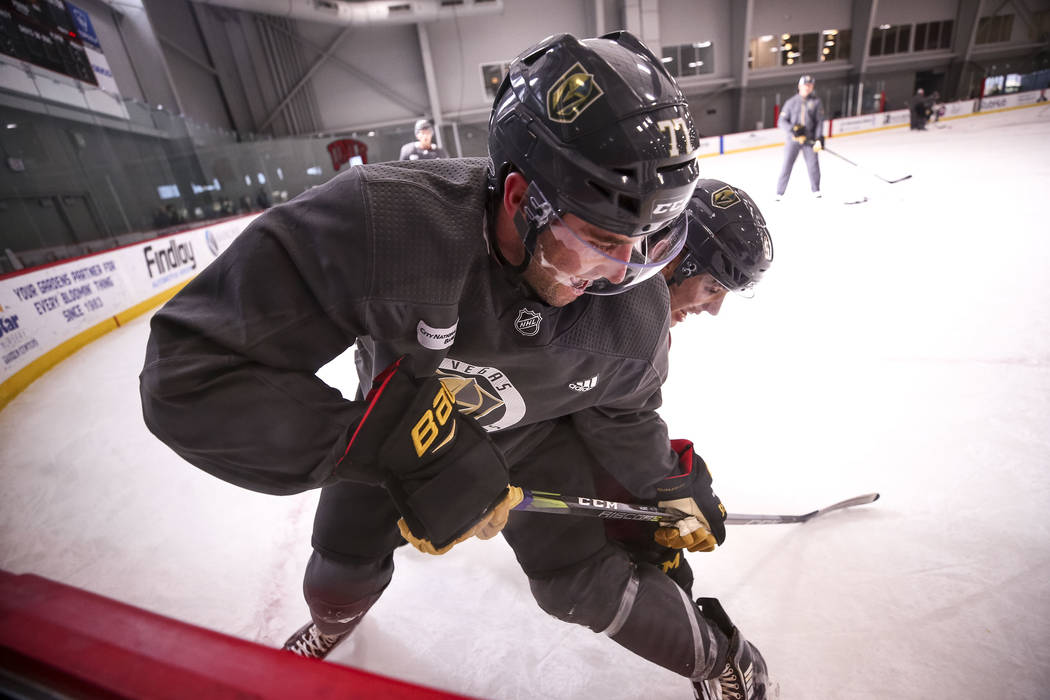 Vegas Golden Knights defenseman Brad Hunt, foreground, and left wing David Perron vie for the puck during the NHL team's practice at the City National Arena in Las Vegas, Wednesday, Dec. 6, 2017.  ...