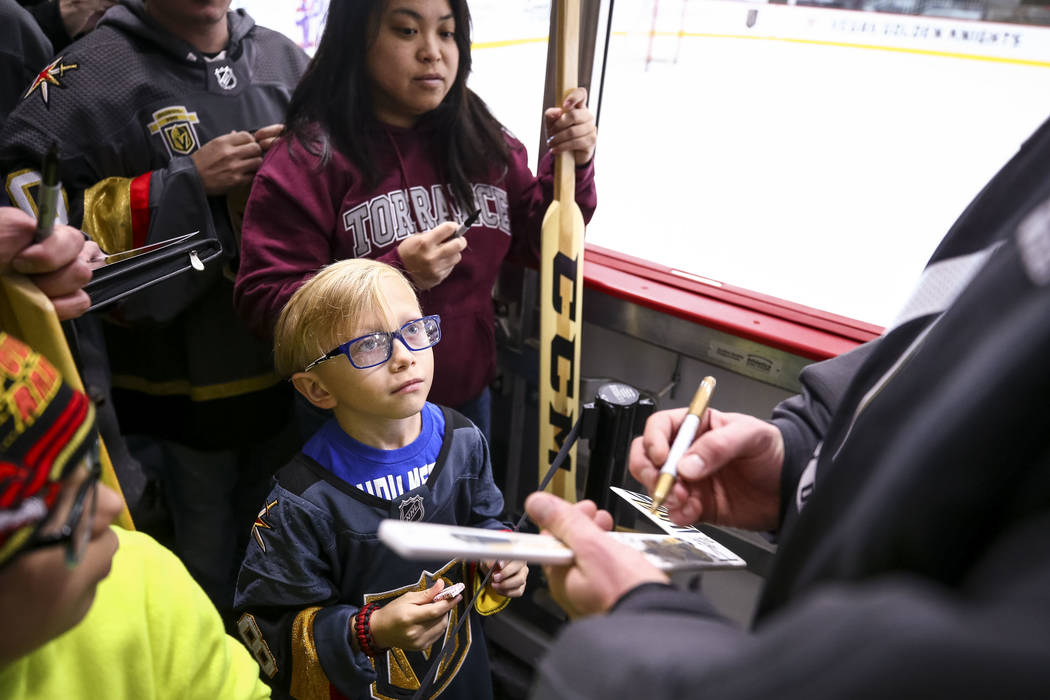 Las Vegas resident Gavin Trudell, 8, looks up at Golden Knights goalie Marc-Andre Fleury as he gets an autograph on his hockey stick following the NHL team's practice at the City National Arena in ...