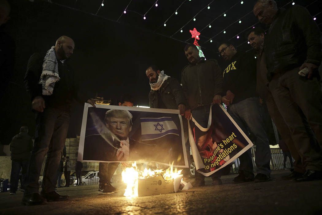 Palestinian hold poster of the President Donald Trump during a protest in Bethlehem, West Bank, Tuesday, Dec. 6, 2017. (AP Photo/Mahmoud Illean)
