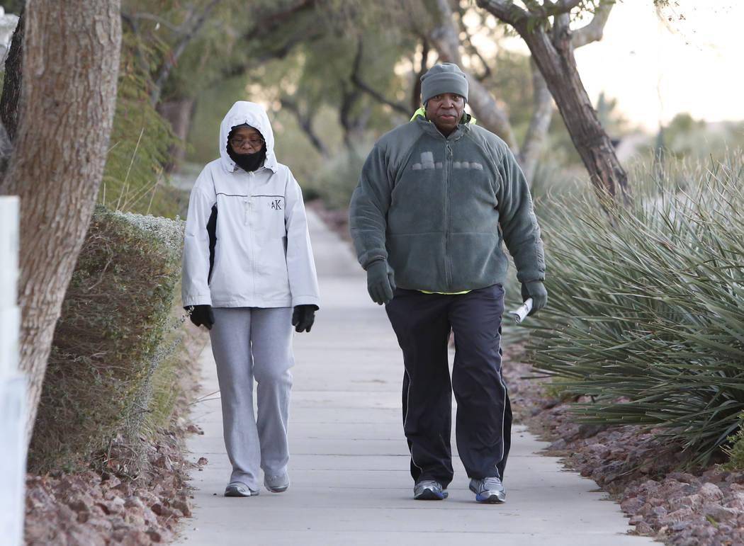 Joann Kemp and her husband, Gary, walk along Seven Hills Drive during a cold morning on Wednesday, Dec 6, 2017, in Henderson. (Bizuayehu Tesfaye/Las Vegas Review-Journal) @bizutesfaye