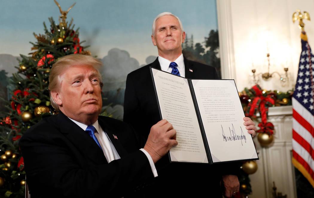After signing, U.S. President Donald Trump holds up the proclamation that the United States recognizes Jerusalem as the capital of Israel and will move its embassy there, during an address from th ...